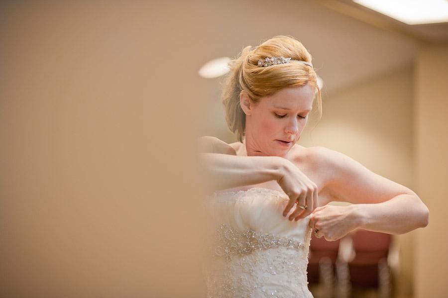 bride fixing dress at church