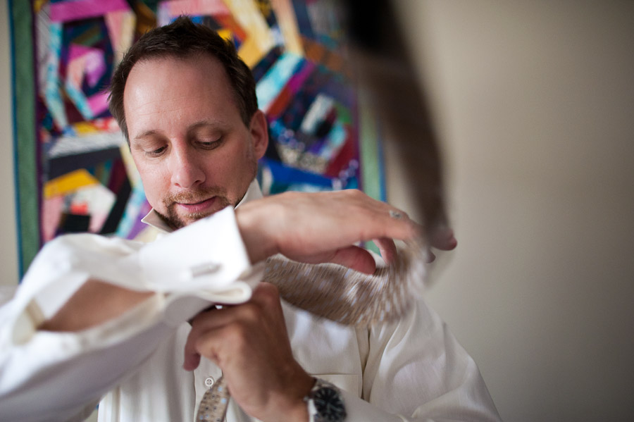 groom flipping tie while getting ready for wedding