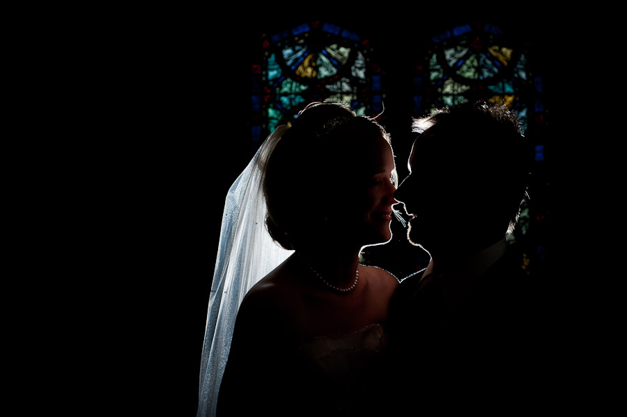 strobist portrait of bride and groom in front of stained glass