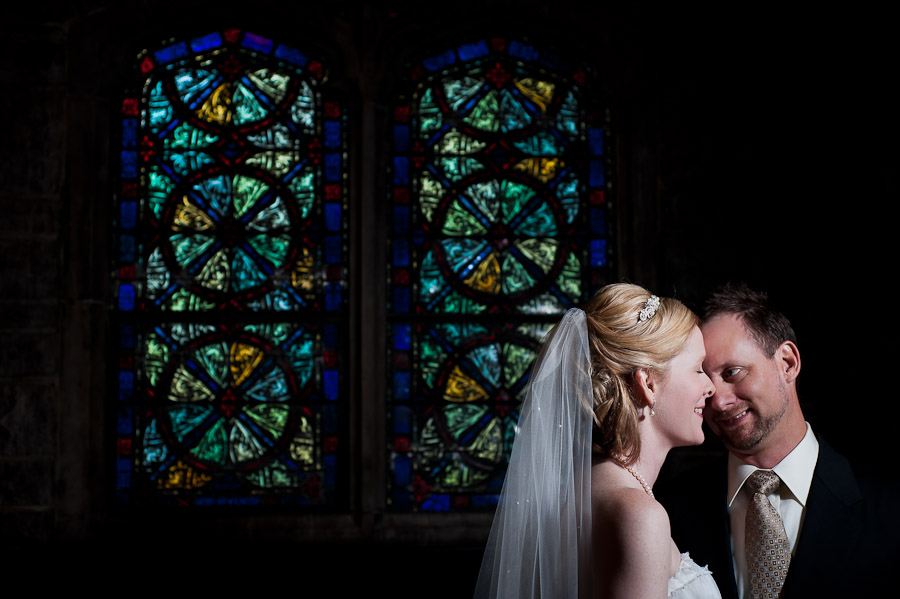 strobist portrait of bride and groom with stained glass