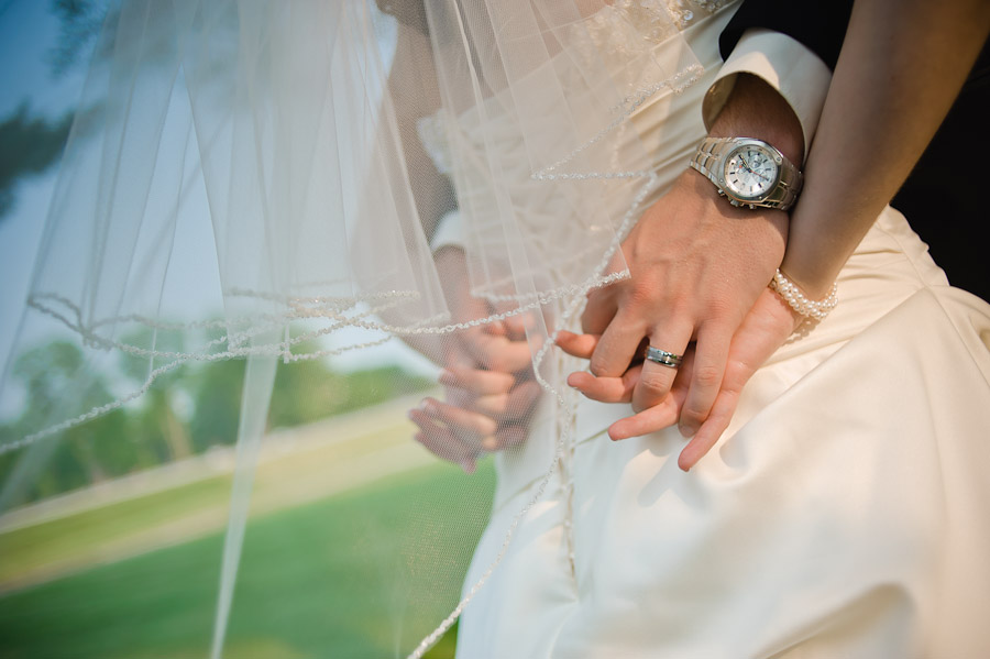 groom and bride holding hands with veil in wind
