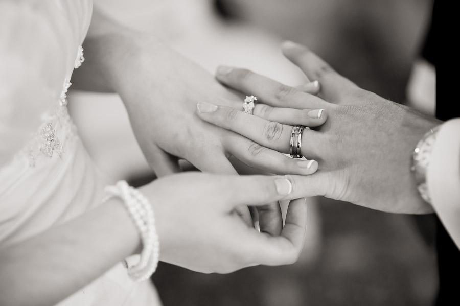 bride and groom looking at wedding rings