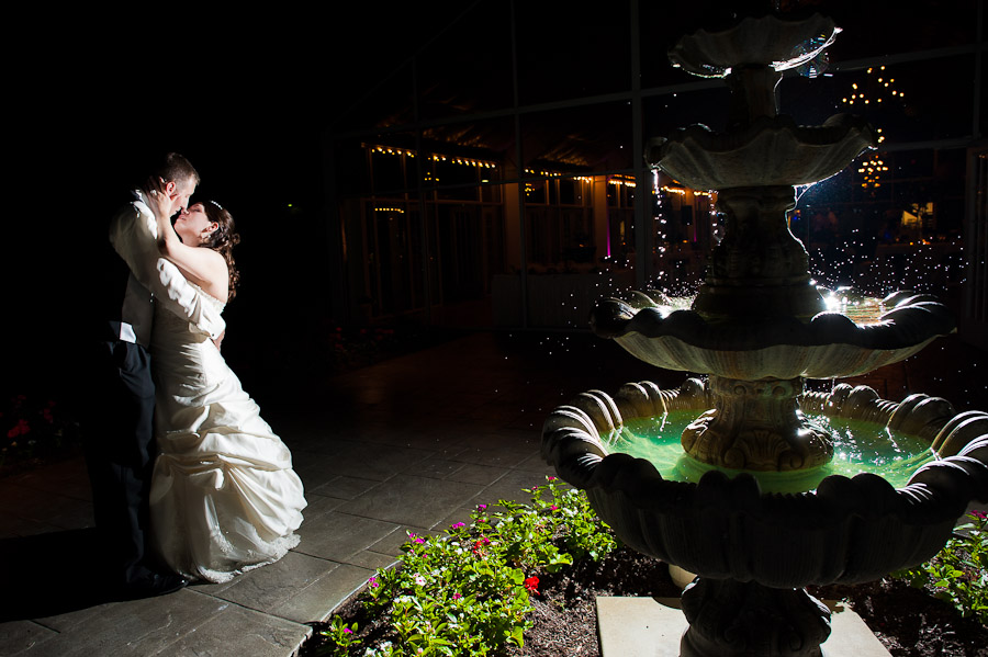 elegant strobist portrait of bride and groom at night next to fountain