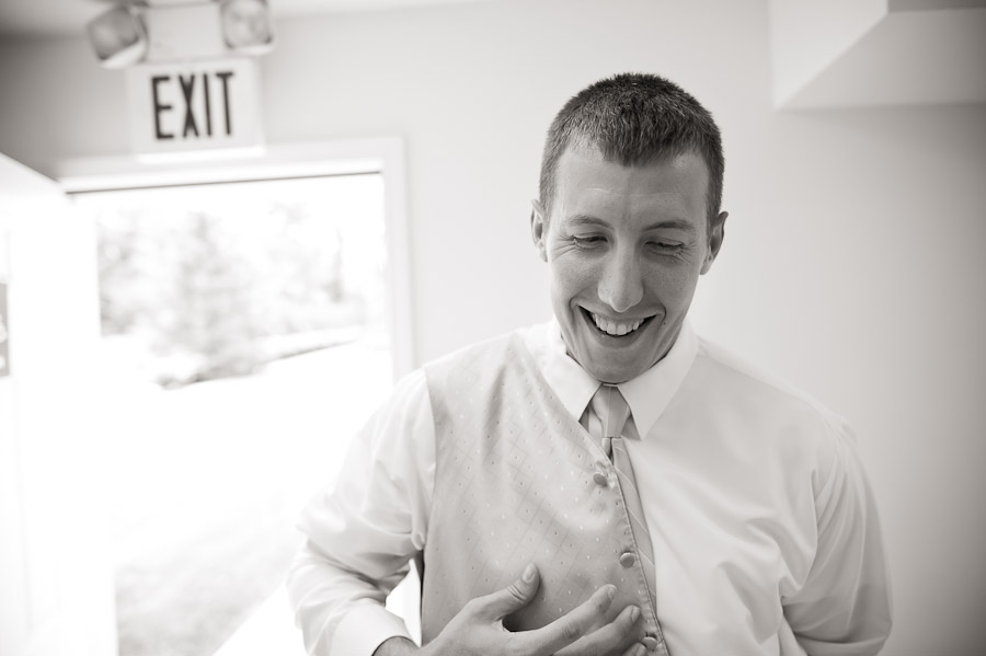 groom putting on vest before indianapolis wedding