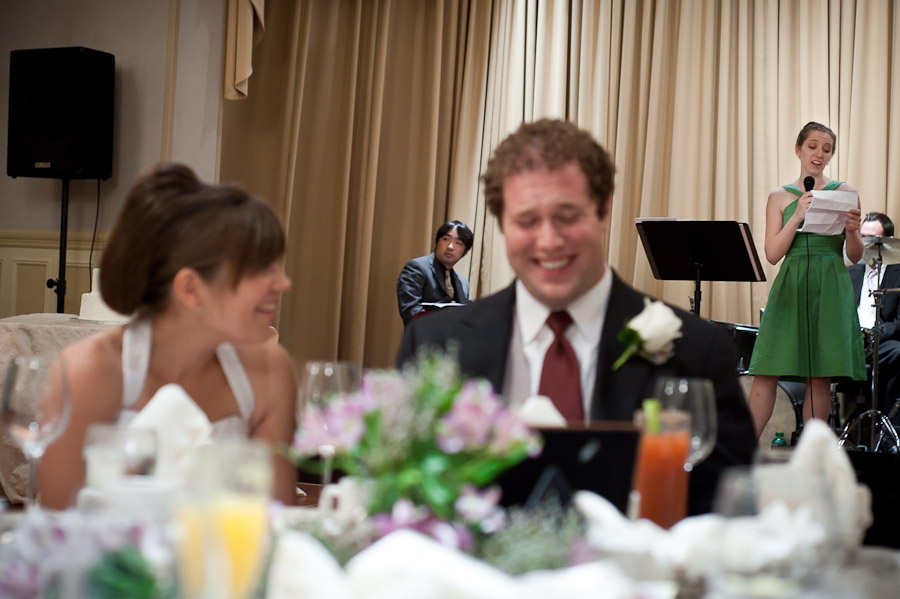 funny moment of bride and groom laughing during toast