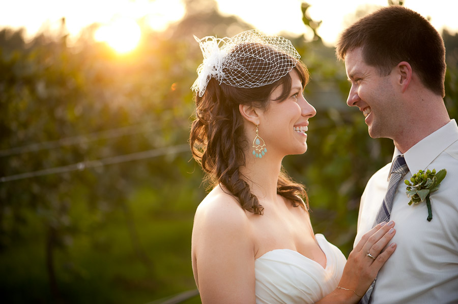 bride and groom smiling at sunset