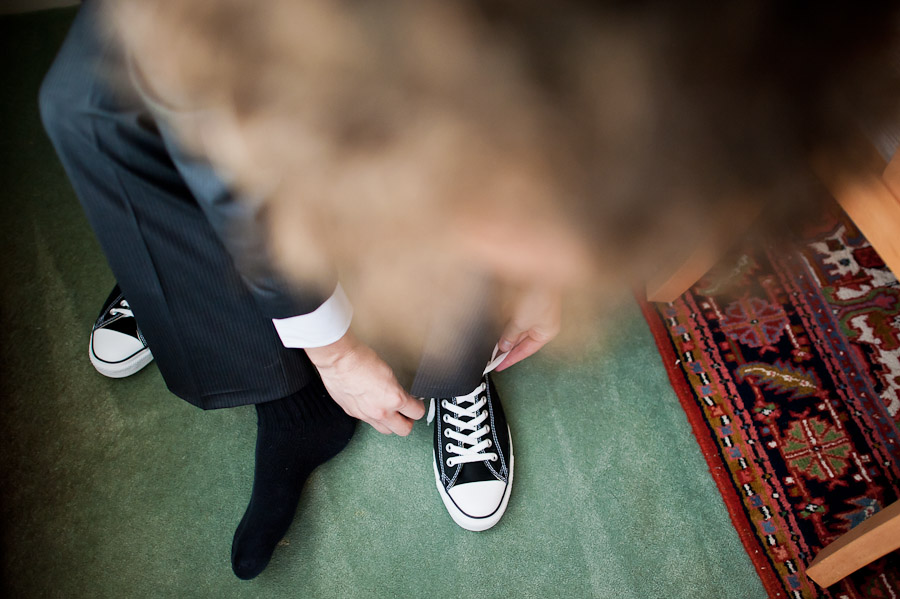 Groom putting on chuck taylor's