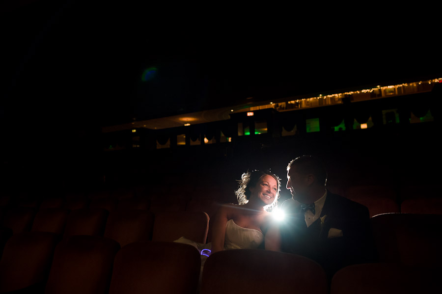 Creative and fun portrait of wedding couple in theater