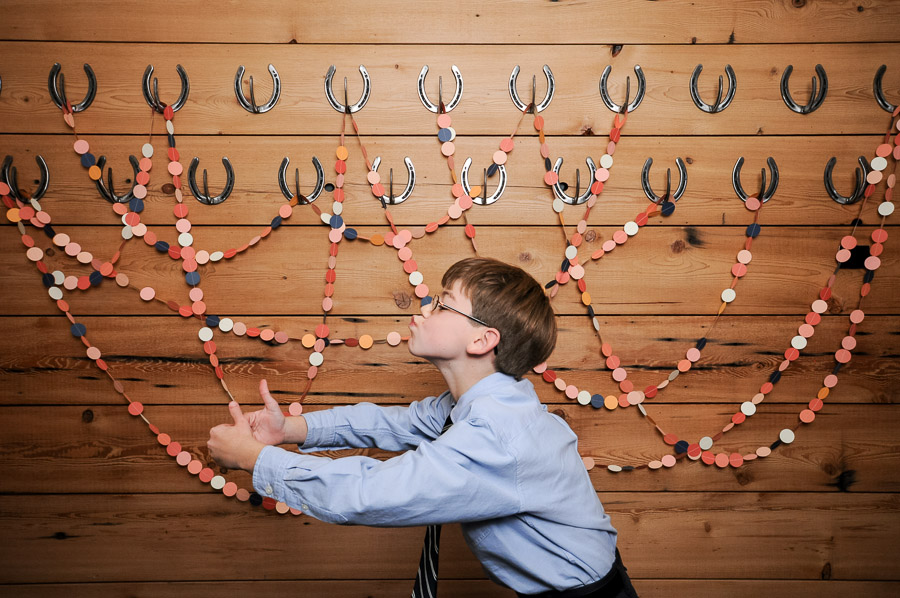 Really hilarious photo of funny kiddo in photobooth with streamers and horseshoes