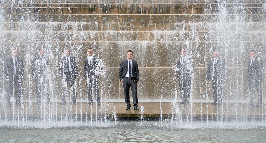 Fun groomsmen portrait behind water