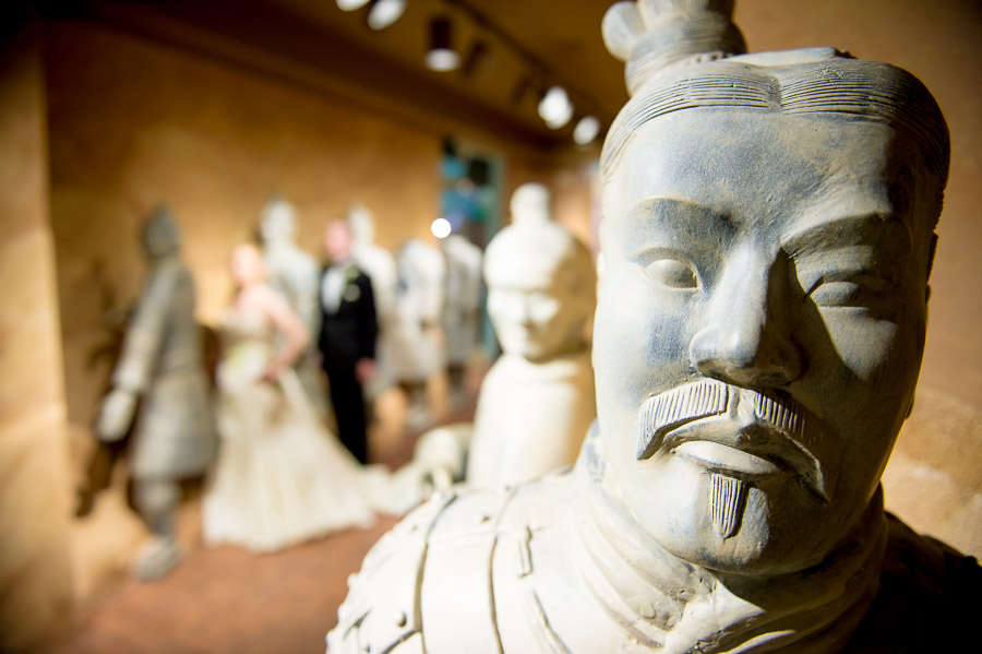 Hilarious wedding portrait of bride and groom in children's museum with statues