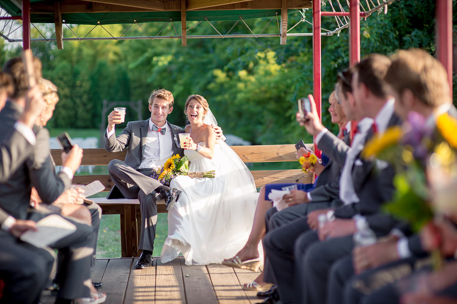 bride, groom and bridal party on tractor after wedding ceremony at apple orchard