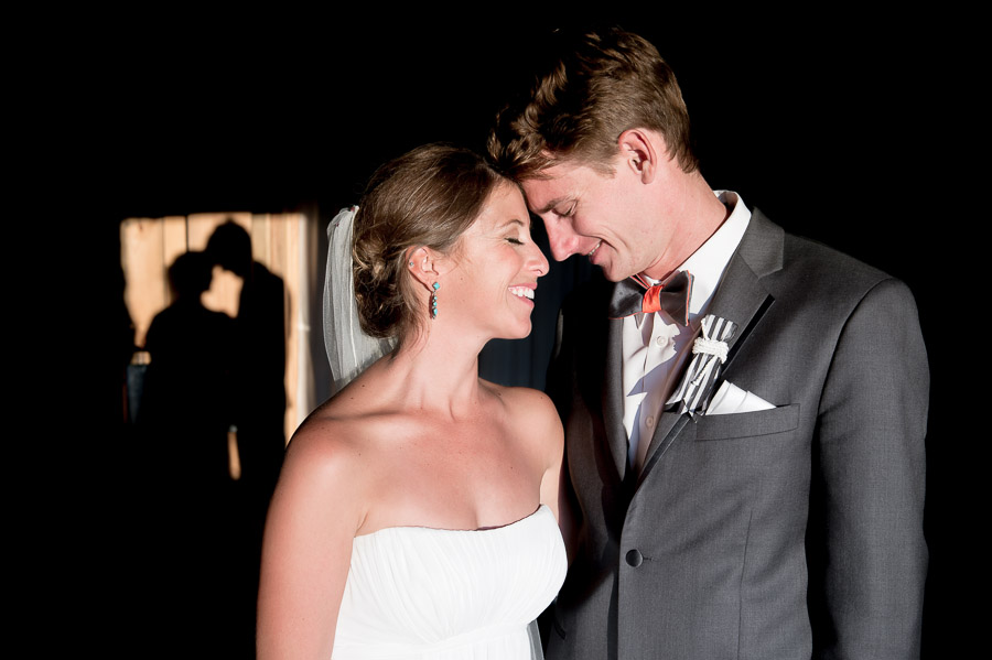 creative and romantic bride and groom photo in barn with shadows