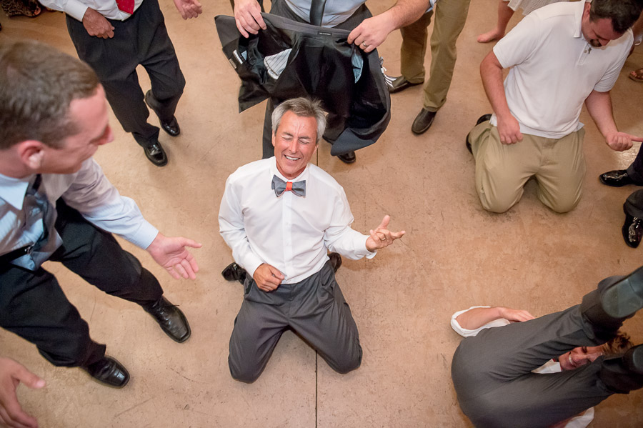 Hilarious photo of father of the bride playing air guitar at wedding reception at apple orchard