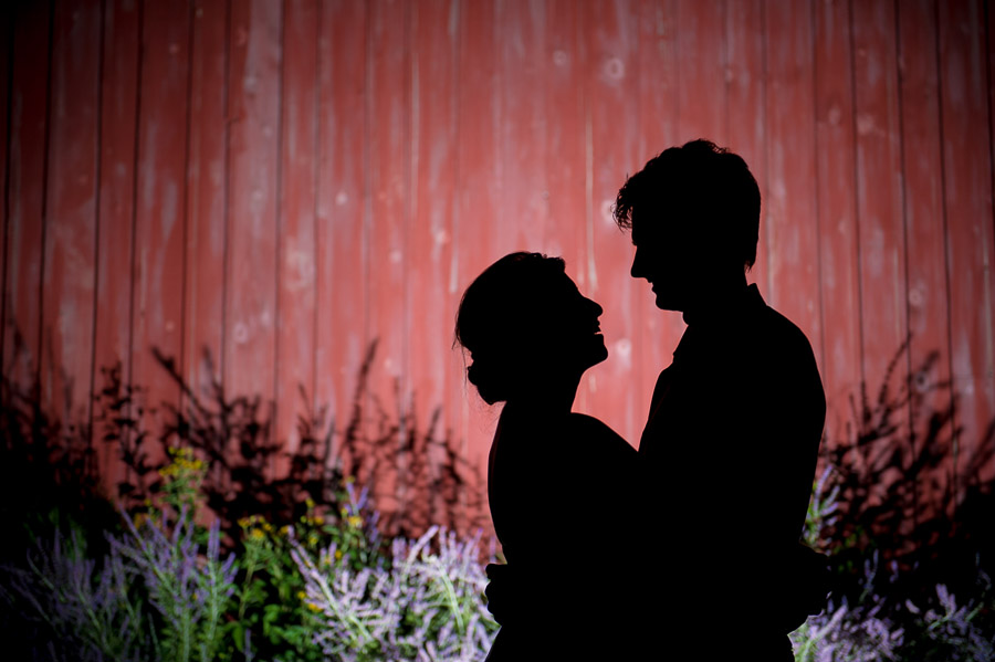 Romantic silhouette of bride and groom against barn at Indiana orchard wedding