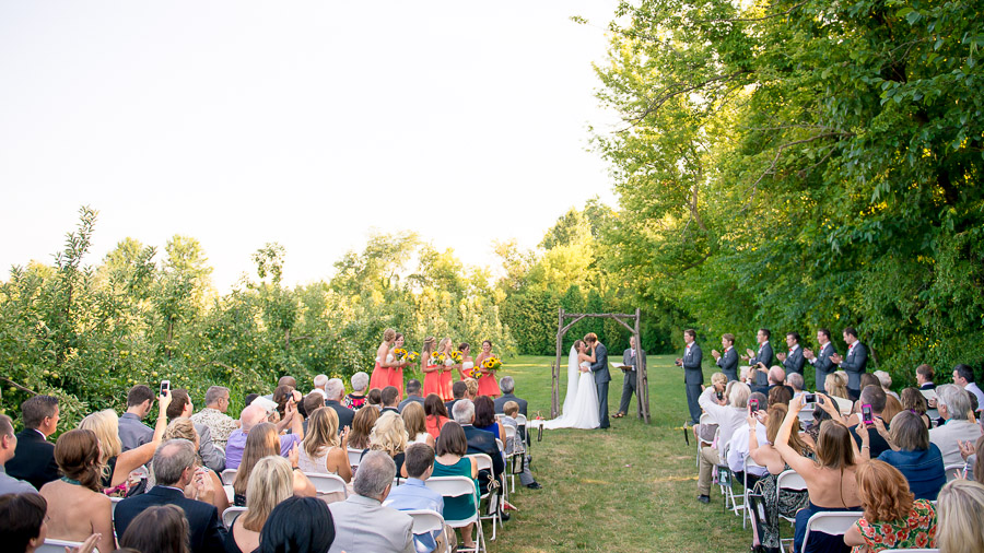 romantic and colorful summer wedding ceremony in apple orchard in the midwest