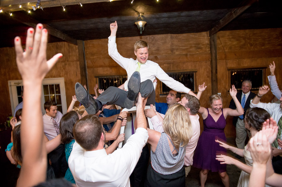 fun, wild, energetic dance floor photo with groom in the air at Bluemont Vineyard wedding