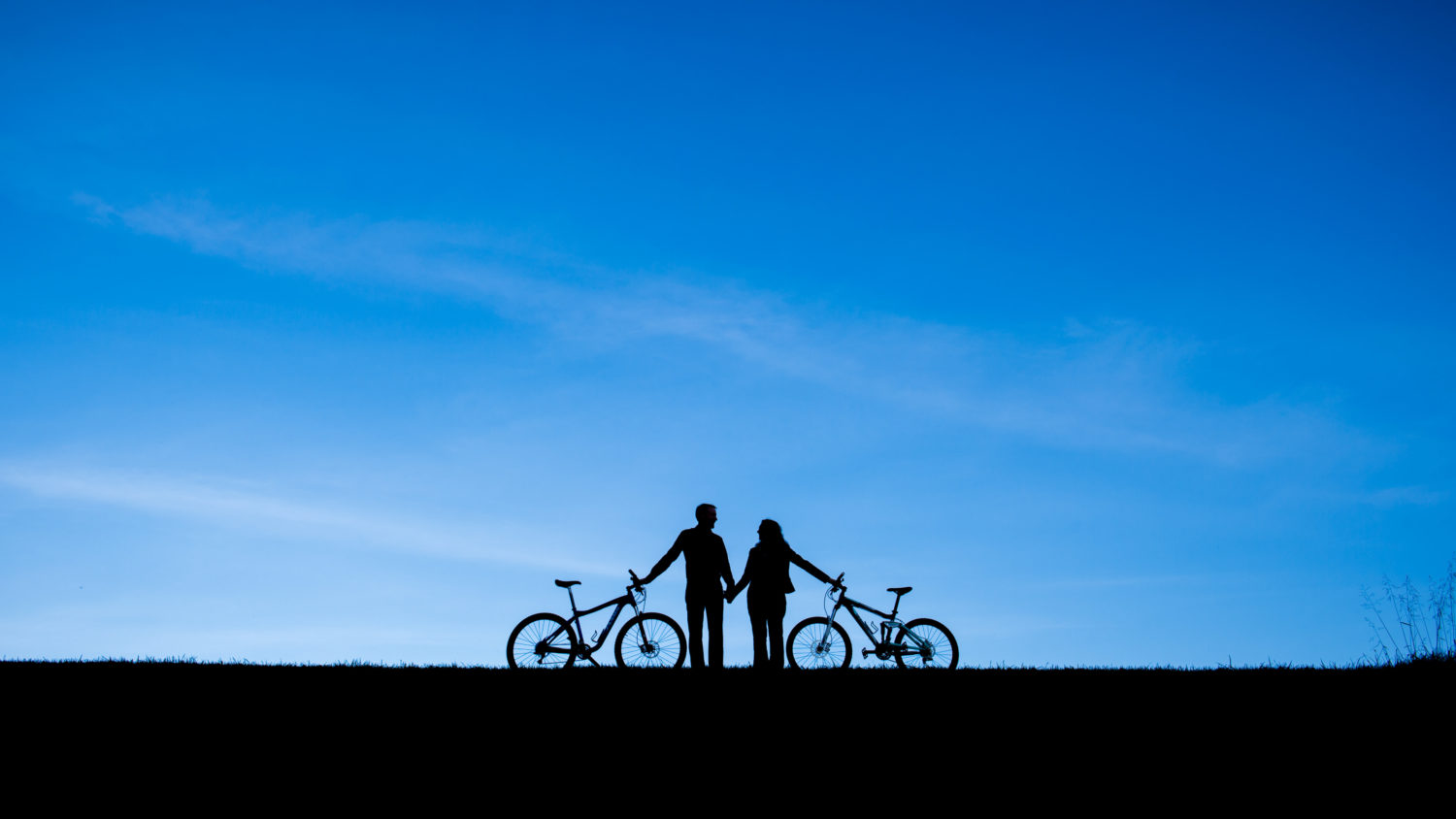 Minimalistic and silhouetted engagement photo with bikes