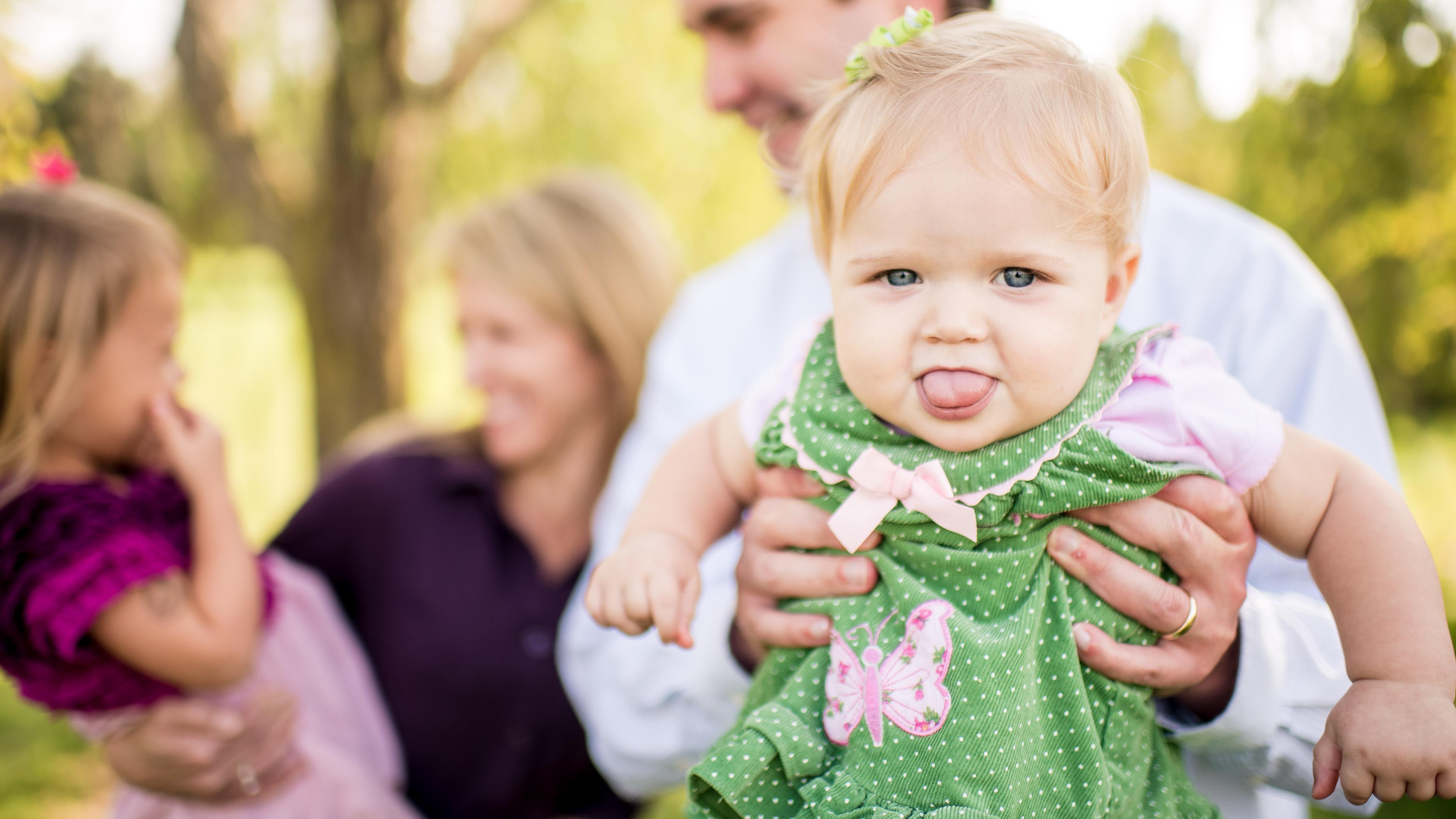 Funny baby tongue at family photoshoot