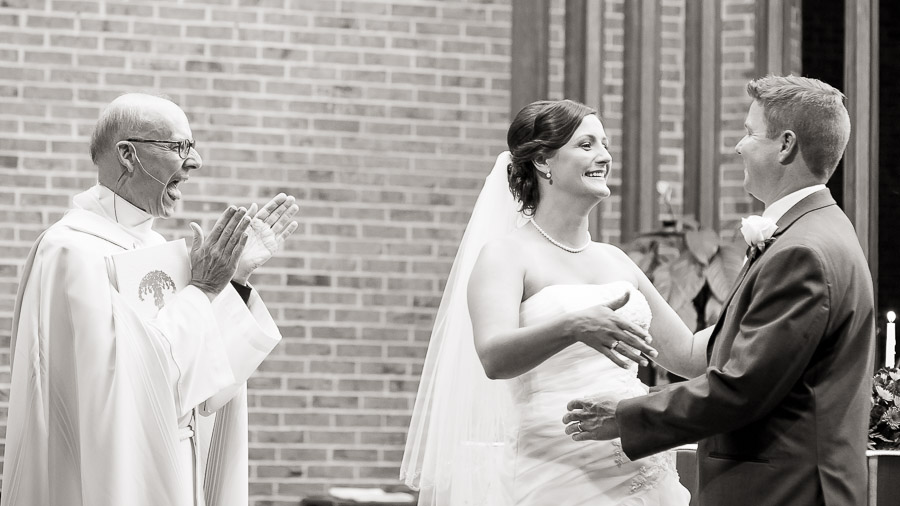 Very happy priest and newly married couple at Christ the King church