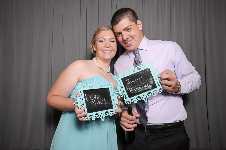 Very funny photobooth photograph with chalkboards and gray background at Indiana wedding