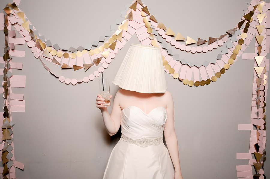 Hilarious photobooth pic of bride with lampshade on her head and geometric paper garland background