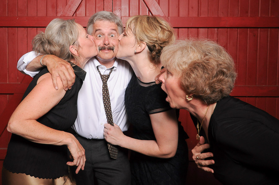 Tall + small Photobooth photo of very happy dude getting kisses at Indiana wedding
