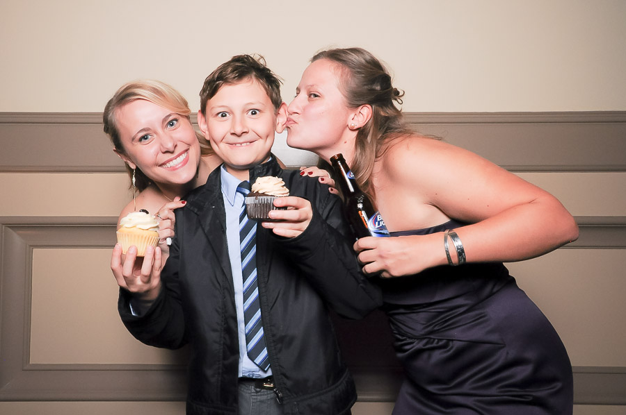 Cute photobooth photo of happy boy getting kisses and cupcakes! At wedding in Richmond, Virginia.