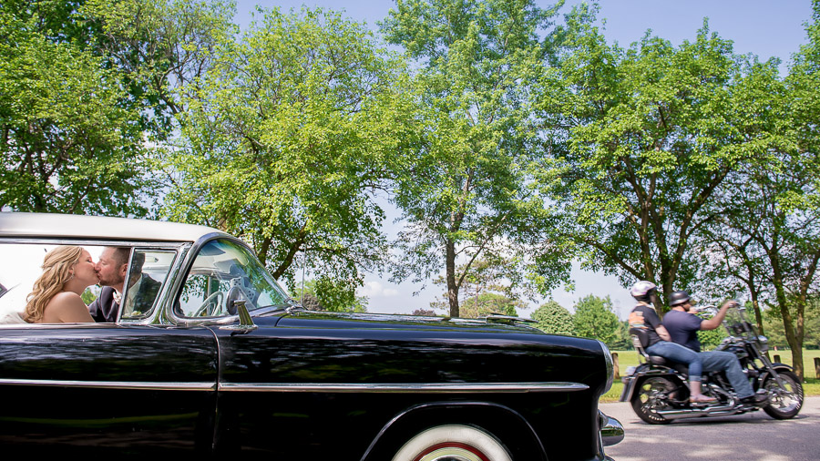 Awesome wedding portrait in classic car with motorcycle photobomb in Indiana