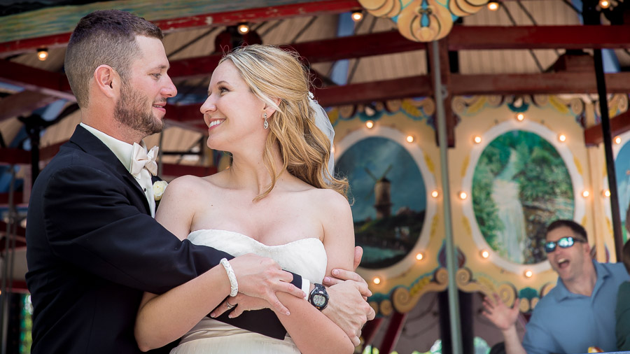 funny photobomb of wedding couple by dude on carousel at Indiana wedding