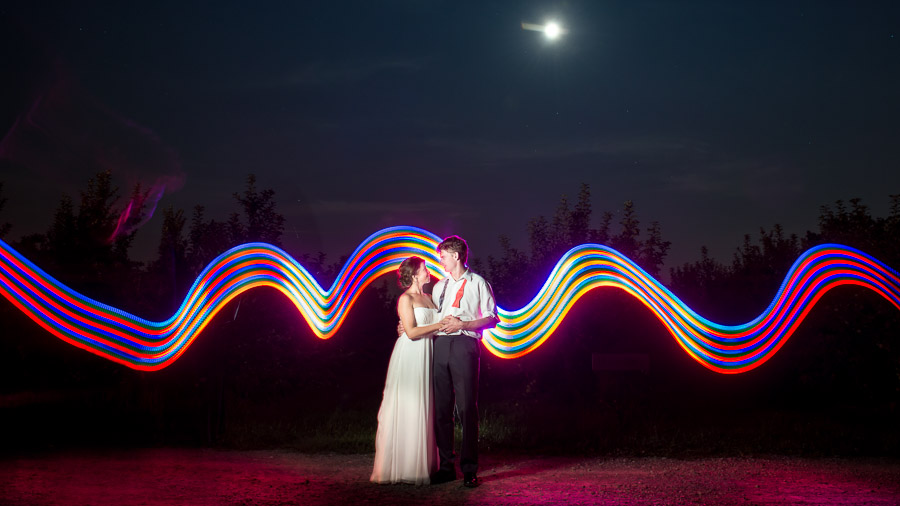 Fun, colorful light painting with bride and groom in orchard by TALL + small Photography