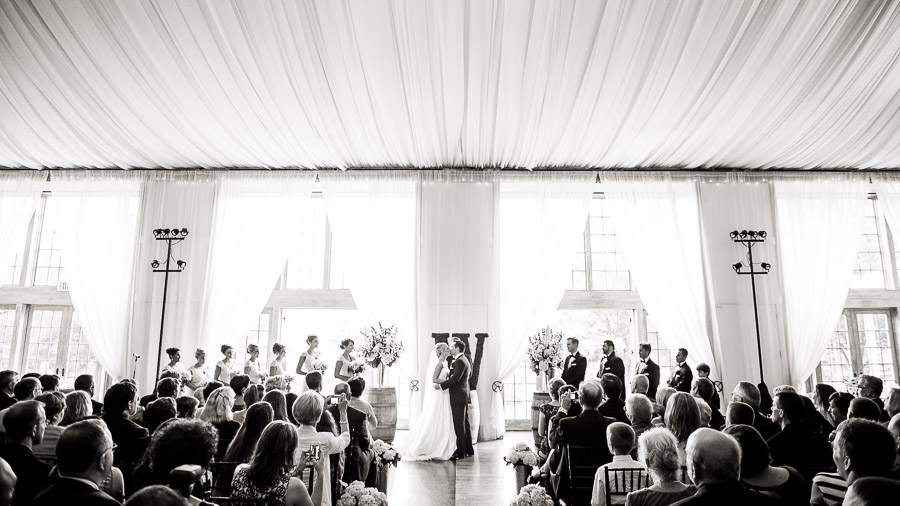 First kiss photo indoors at Veritas Vineyards wedding ceremony by Tall and Small Photography