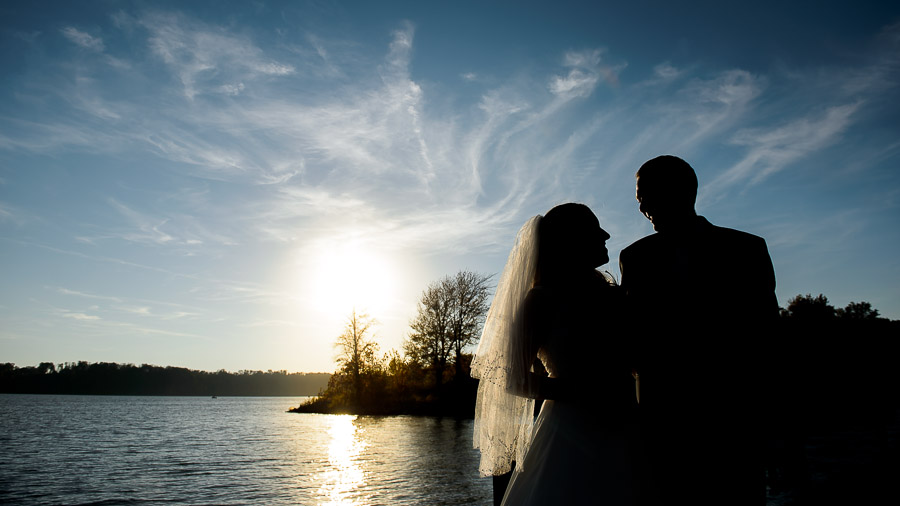 Gorgeous bride and groom portrait with sunset on Lake Monroe