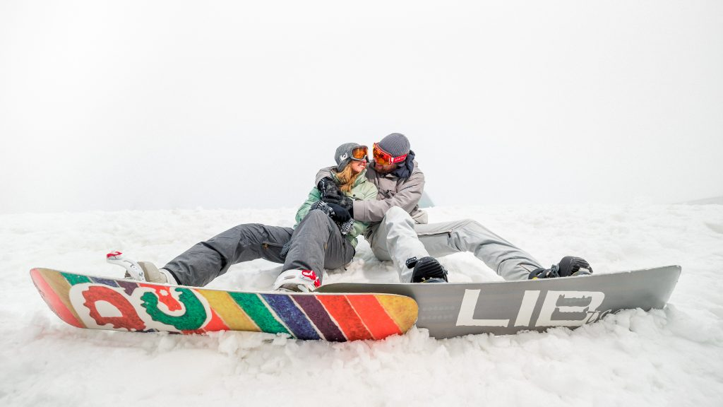 A couple at their snowshoe engagement photo shoot sitting down with snowboards.