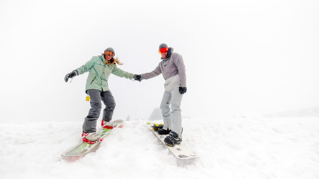 A couple snowboarding downhill holding hands.