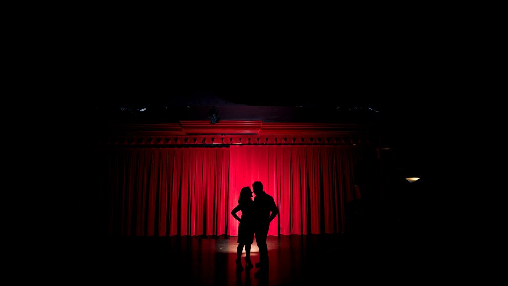 Rachel + Travis spotlit at a theater