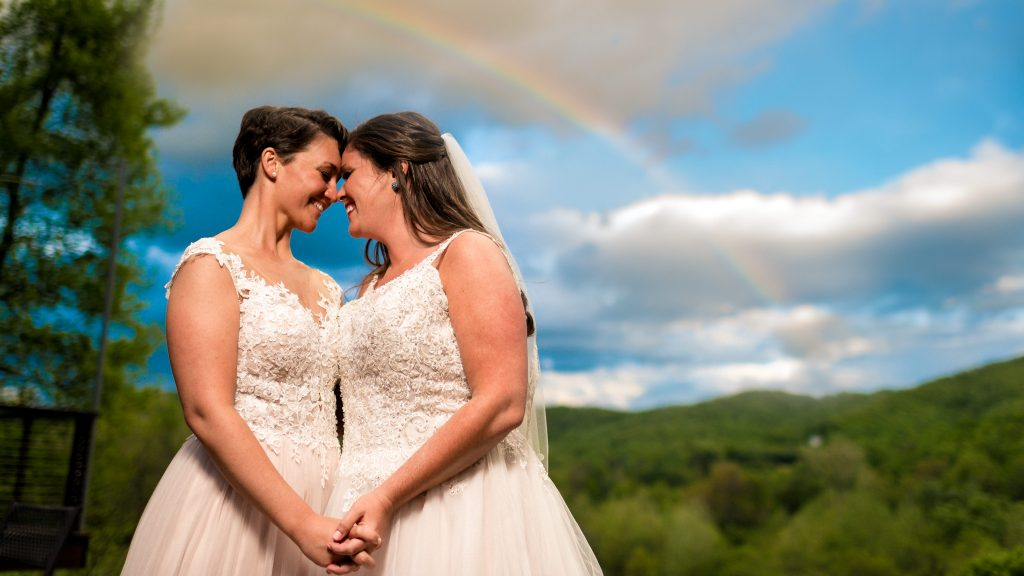 Ashley + Sarah under a rainbow right after there ceremony at their Bold Rock wedding